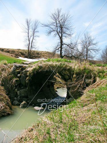 Pont tube métal laissant couler rivière